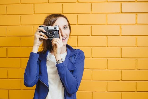 Belle femme folle avec appareil photo argentique rétro sur mur de briques jaunes