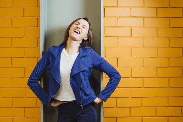 Belle femme folle moderne joyeuse sur mur de briques jaunes