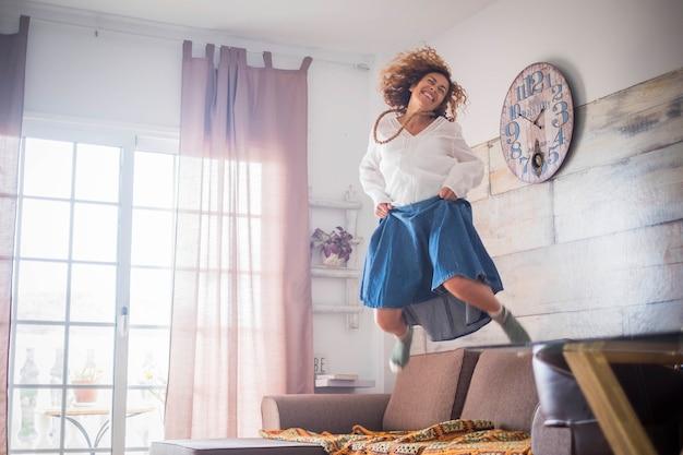 Belle femme folle solitaire d'âge moyen sautant à la maison pour la satisfaction ou la victoire. souriez beaucoup et amusez-vous avec un grand saut sur le canapé. concept de liberté et d'indépendance