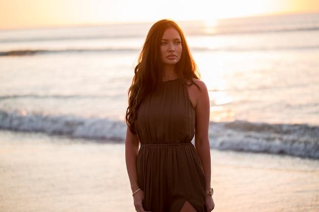 Belle femme sur fond de coucher de soleil