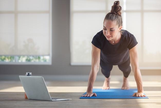 Belle femme en forme faisant de la planche de yoga et regardant des tutoriels en ligne sur son ordinateur portable
