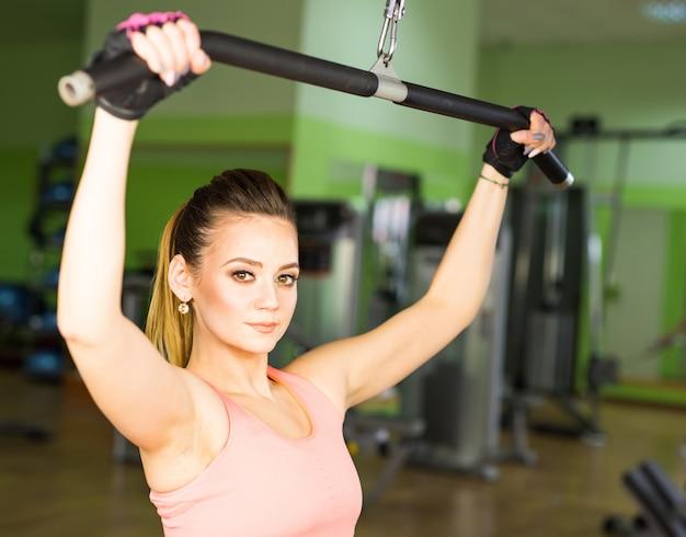 Belle femme en forme musculaire exerçant la musculation dans la salle de gym