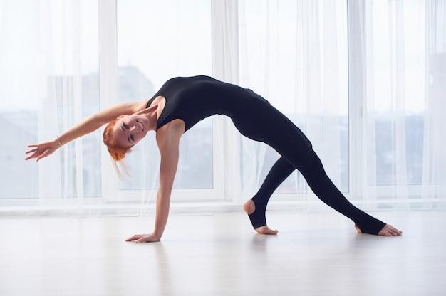 Belle femme en forme sportive pratique le yoga asana camatkarasana