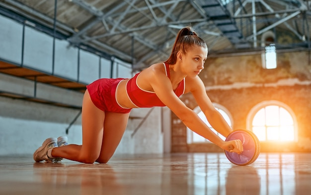 Belle femme forte dans les trains de vêtements de sport avec roue d'exercice dans la salle de gym ou le club. concept de sports et de loisirs.