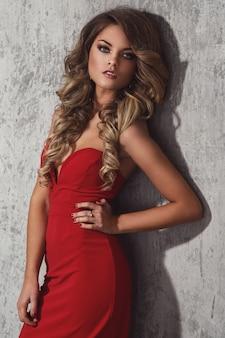 Belle femme frisée en robe rouge