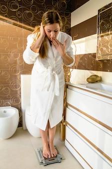 Belle femme frustrée debout sur une échelle de salle de bain malheureuse et inquiète de son poids. concept de surpoids et de régime.