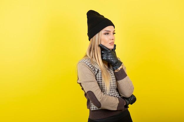 Belle femme en gants noirs et chapeau pensant sur le jaune.