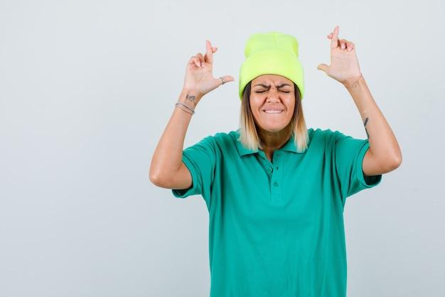 Belle femme gardant les doigts croisés en t-shirt polo, bonnet et à la chance, vue de face.