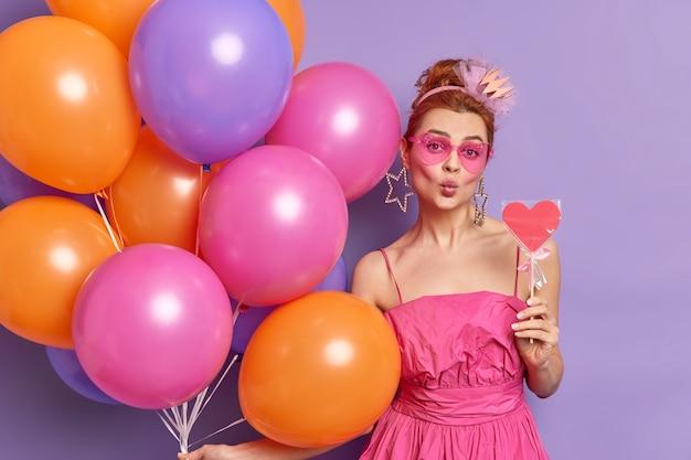 Belle femme garde les lèvres arrondies a une humeur romantique tient une sucette savoureuse