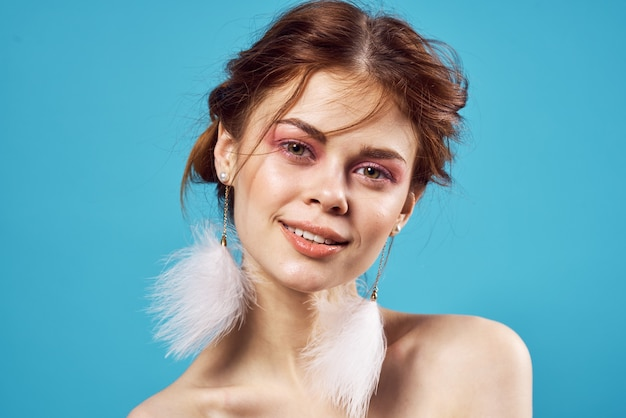 Belle femme glamour épaules nues boucles d'oreilles luxe close-up fond bleu