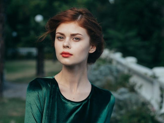 Belle femme glamour robe verte luxe lèvres rouges à l'extérieur.