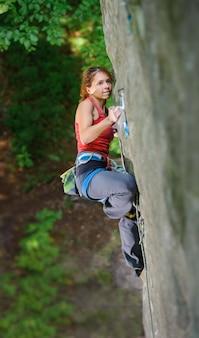 Belle femme grimpeur escalade raide rocher avec une corde