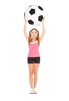 Belle femme avec un gros ballon de football sur un mur blanc