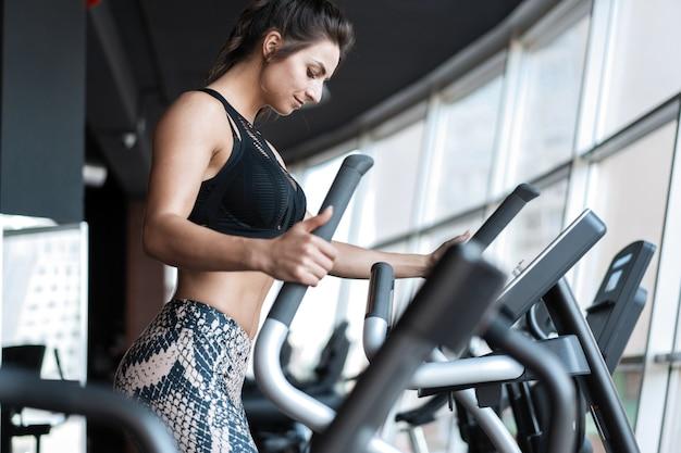 Belle femme de gym exerçant sur une machine cardio souriant