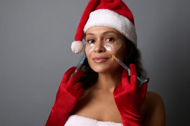 Belle femme habillée en père noël pour les vacances de noël, tient des seringues près de son visage, prête pour des injections de beauté sur ses plis nasogéniens. concept anti-âge, lifting et rajeunissement du visage pour l'annonce