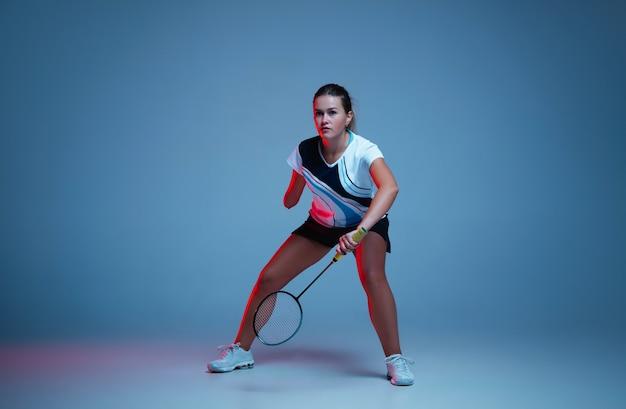Belle femme handicap pratiquant le badminton isolé sur fond bleu à la lumière du néon