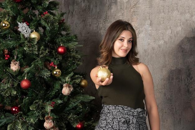 Belle femme en haut noir posant avec une boule dorée près de l'arbre de noël