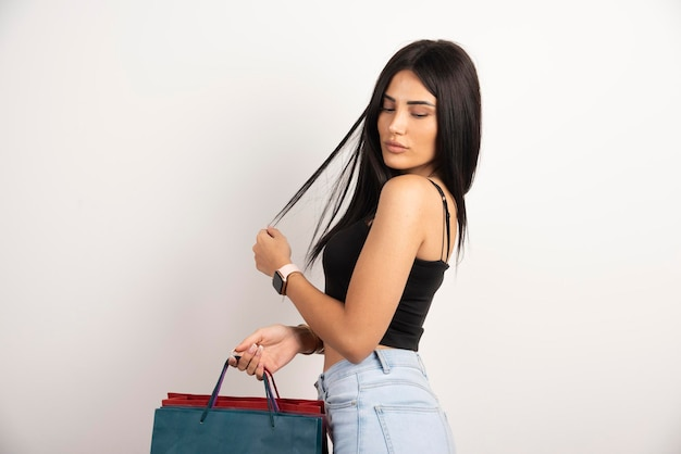 Belle femme en haut noir posant avec des sacs à provisions. photo de haute qualité