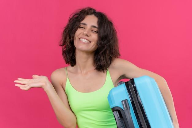 Une belle femme heureuse aux cheveux courts portant un haut court vert tenant une valise bleue