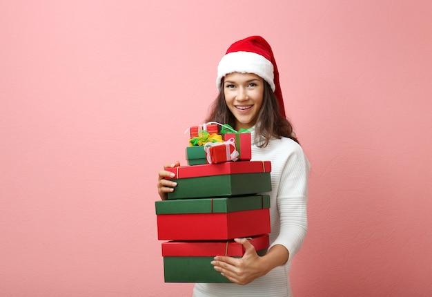 Belle femme heureuse avec des cadeaux de noël sur un mur rose