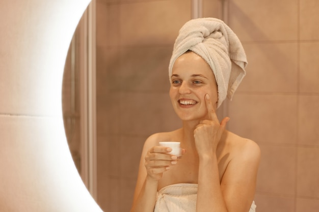 Belle femme heureuse dans un miroir frottant de la crème cosmétique sur son visage, mettant de l'argent hydratant sur sa peau dans la salle de bain, exprimant des émotions positives tout en ayant des procédures de beauté.
