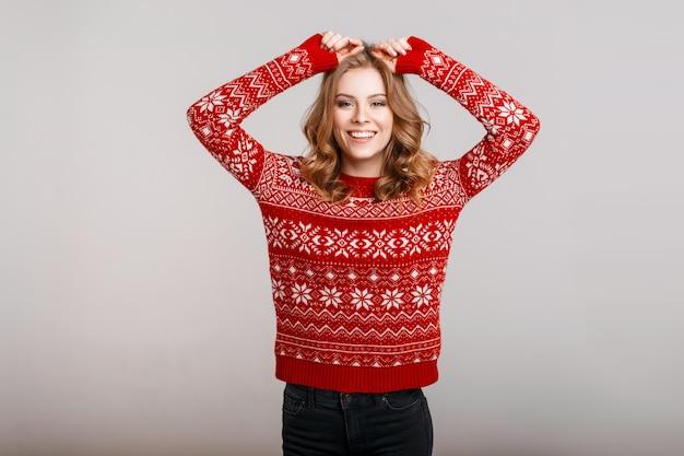 Belle femme heureuse drôle dans un beau pull vintage d'hiver avec un ornement sur fond gris