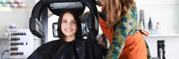 Belle femme heureuse est assise sur une chaise et sèche les cheveux