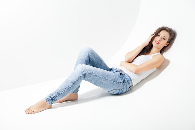 Belle femme heureuse en jeans posant sur blanc