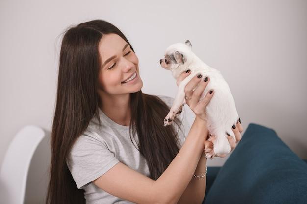 Belle femme heureuse jouant avec son chiot chihuahua à la maison
