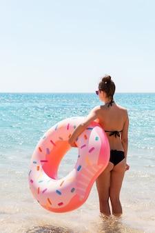 Belle femme heureuse mignonne sexy courant sur la plage avec un anneau gonflable en caoutchouc rose dans la main. vacances d'été et concept de vacances.