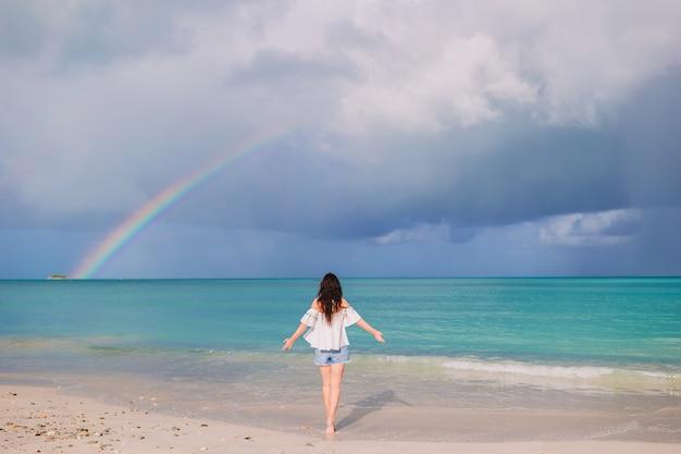 Belle femme heureuse sur la plage avec bel arc-en-ciel sur la mer