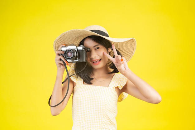 Une belle femme heureuse portant un grand chapeau et une caméra sur un jaune.