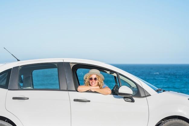 Une belle femme heureuse regardant la caméra de l'intérieur d'une voiture avec la mer ou l'océan sur les lieux