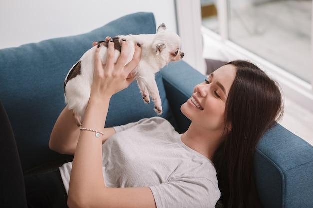Belle femme heureuse se détendre à la maison sur le canapé, jouant avec son mignon petit chien chihuahua