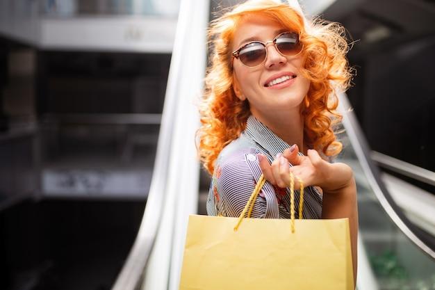 Belle femme heureuse shopping tenant des sacs à provisions.
