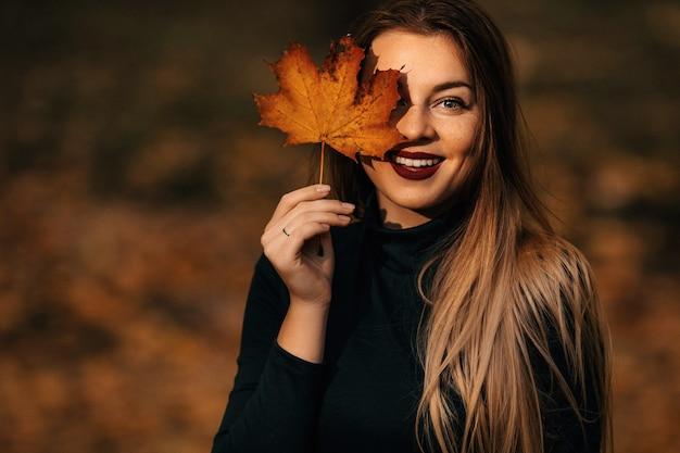 Belle femme heureuse avec un sourire tient une feuille jaune d'automne près du visage