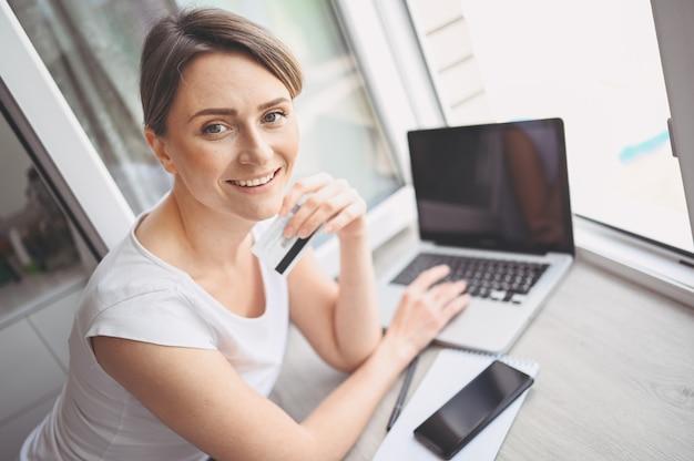 Belle femme heureuse tenant la carte de crédit à la main et à l'aide du clavier d'ordinateur portable. femme d'affaires ou entrepreneur travaillant. achats en ligne, commerce électronique, services bancaires par internet, concept d'argent de poche