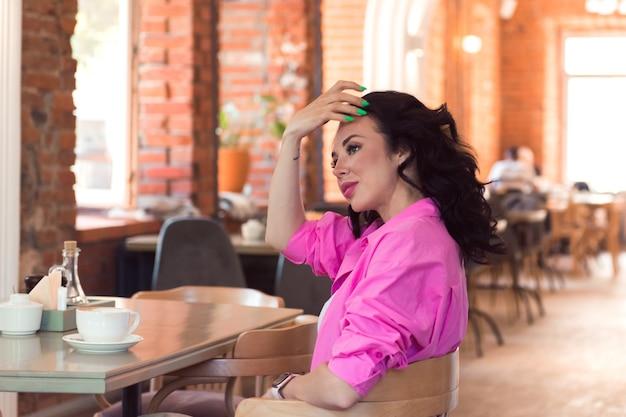 Belle femme heureuse en vêtements roses utilisant des sms sur smartphone avec un ami ou une conversation vidéo