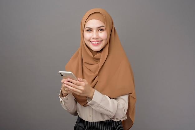 Belle femme avec hijab à l'aide du téléphone