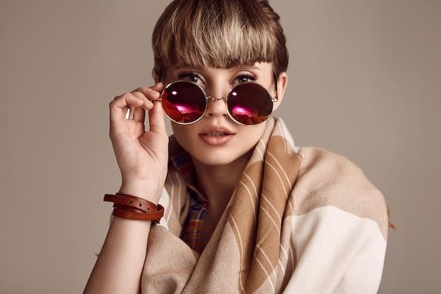 Belle femme hippie blonde glamour avec des lunettes vives