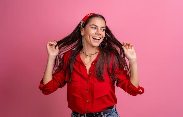 Belle femme hispanique en chemise rouge posant souriant sur rose isolé portant un bandeau