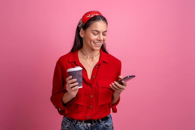 Belle femme hispanique en chemise rouge souriant tenant un smartphone buvant du café sur rose isolé portant un bandeau