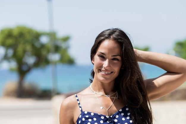 Belle femme hispanique en robe bleue debout contre la mer tout en touchant les cheveux