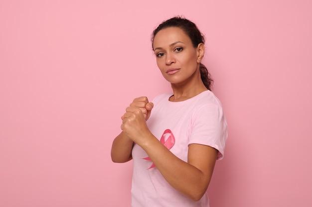 Belle femme hispanique vêtue d'un t-shirt rose et d'un ruban rose de sensibilisation au cancer se tient dans une position de combat pour marquer la lutte contre le cancer, en l'honneur du 1er octobre, regardant la caméra, arrière-plan coloré.