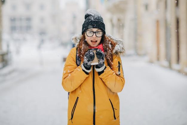 Belle femme d'hiver souriant heureux avec plein air. fille riante à l'extérieur avec boisson chaude