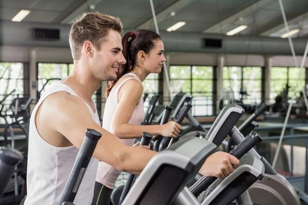Belle femme et homme exerçant sur la machine elliptique