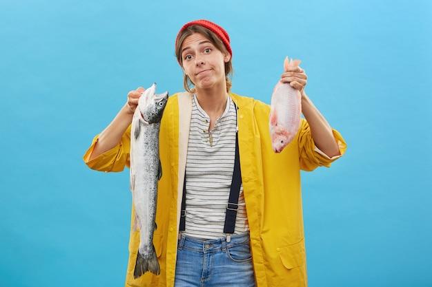 Belle femme en imperméable posant contre le mur bleu avec du poisson frais
