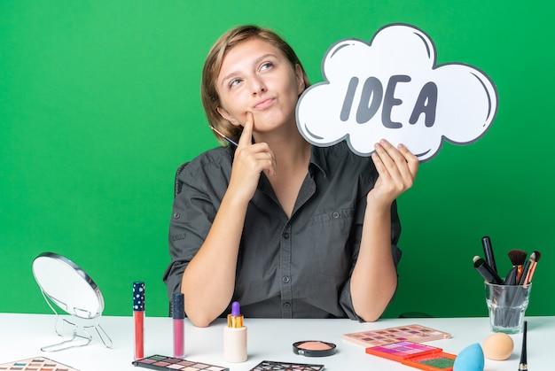 Une belle femme impressionnée est assise à table avec des outils de maquillage tenant une bulle d'idée avec un pinceau de maquillage mettant le doigt dans la joue