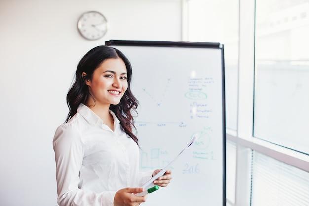 Belle femme indienne dans un environnement d'entreprise présentant devant un tableau blanc