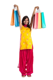 Belle femme indienne portant un sari traditionnel tenant des sacs à provisions
